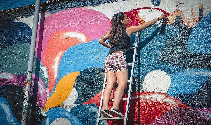 壁に絵を描く女性