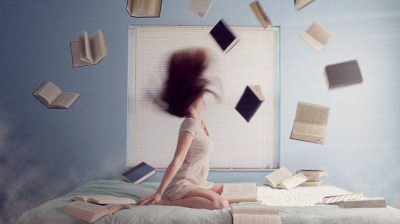 ベッドの上の女性と舞い散る本