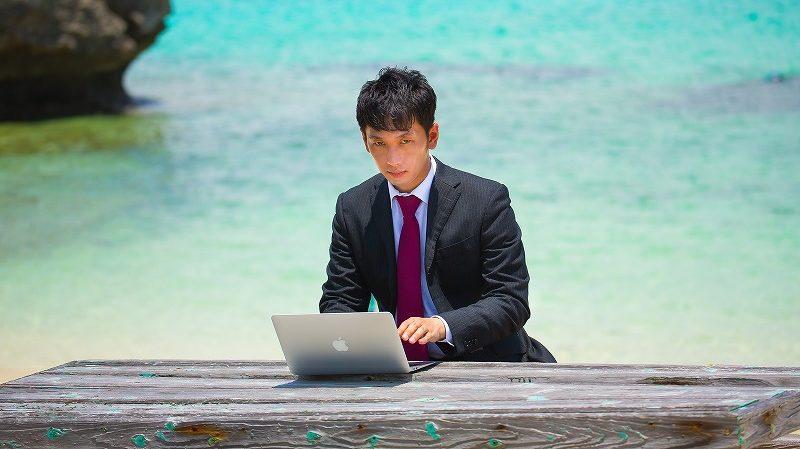 海でパソコンソ使うサラリーマン