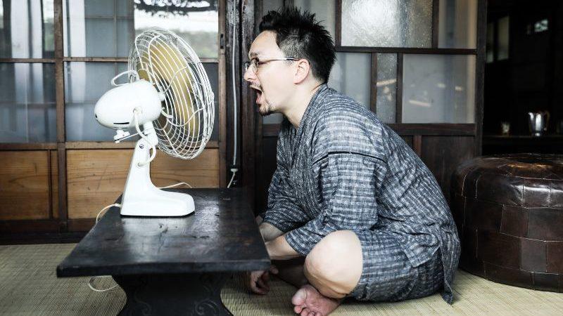 扇風機に当たる男性
